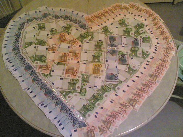 Des billets d'euros dressés sur une table sous forne de coeur