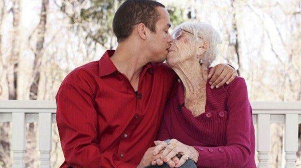 Jeune homme embrassant femme agée
