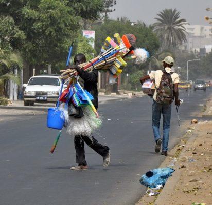 Jeune debrouillard dans la rue vendant objets de menage