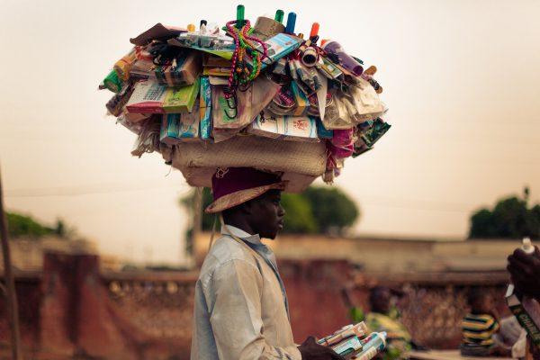 Jeune debrouillard dans la rue avec toutes sortes de marchandises sur la tete.