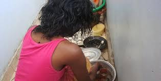 Une jeune fille faisant la vaisselle après un repas.