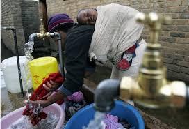 Une Femme entrain de faire la lessive avec son enfant au dos