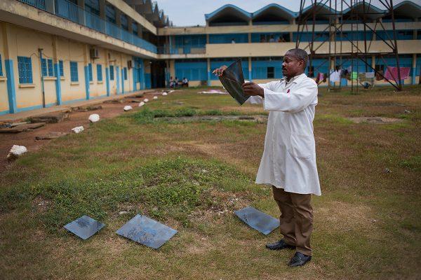 """Departement d'imagerie médicale, Hopital Regional, Ebolowa le 10 fevrier 2015 © Sylvain Liechti """"Si le temps le permet nous séchons les radiographies sur la pelouse"""" Roger Zeupa Nguewoua, technicien en imagerie médicale."""